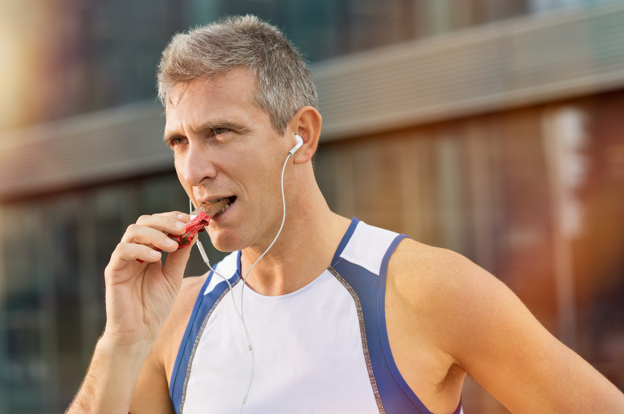 Older, fit man in a white shirt eating chocolate bar after a workout
