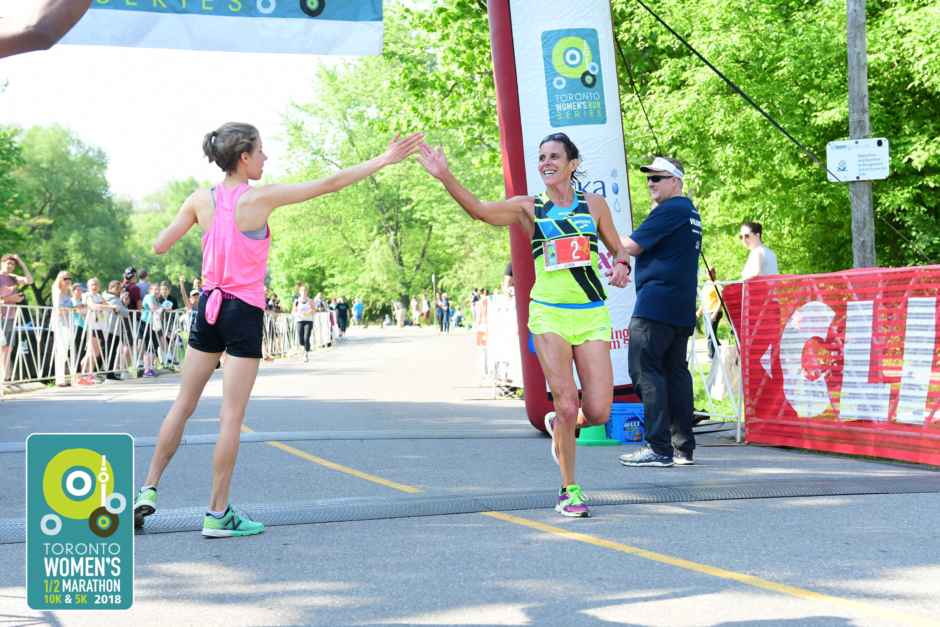 Lisa Bentley crossing finish line in marathon and high fiving volunteer